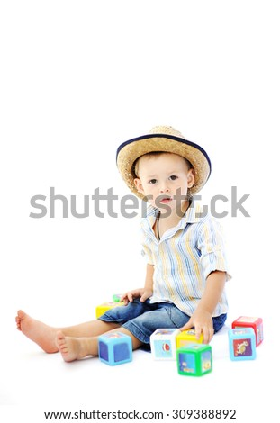baby boy in a straw hat playing with multicolored cubes on a white background - stock photo