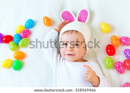 Baby boy in bunny hat lying on green blanket with easter eggs - stock photo