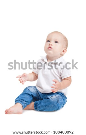 Baby boy in casual sitting on the floor and looking up. Isolated over white
