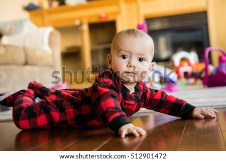 Baby boy in Christmas pajamas learning to crawl