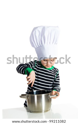 Baby boy in hat of the cook playing with kitchen accessories