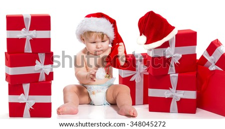 Baby boy in red christmas hat is sitting with many gift boxes. New year. Event. Love. Kid.
