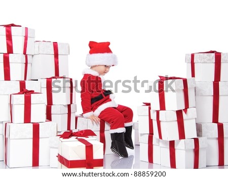 Baby boy in Santa Claus costume sitting on gift boxes - stock photo