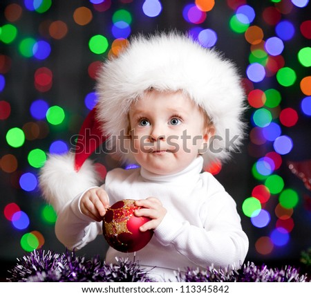 baby boy in Santa Claus hat on bright festive background - stock photo