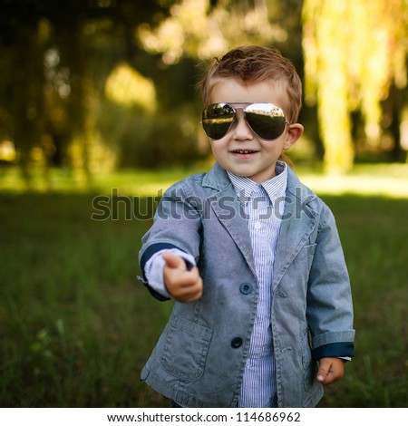 baby boy in the park in sun glasses - stock photo