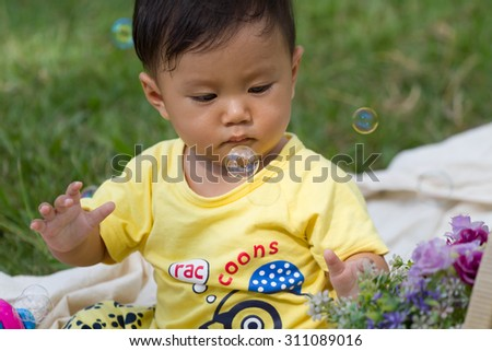 baby boy in yellow shirt sit and play bubble - stock photo