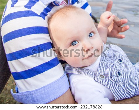 baby boy is making duck face while holding his father's hand in a park in summer time - stock photo
