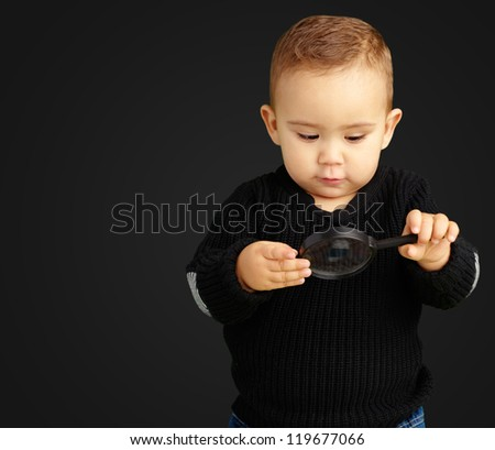 Baby Boy looking at Magnifying Glass against a black background - stock photo
