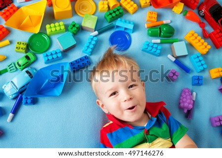 Baby boy lying on blue blanket with many toys around