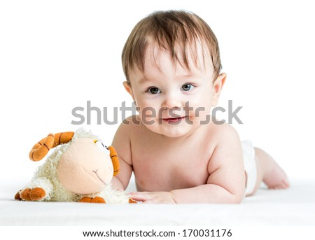 baby boy lying on tummy with lamb toy - stock photo