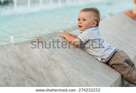 baby boy next to fountain, baby is looking at fountain and water, in front of fountain, looking into the distance, concrete border of fountain, Bibione, Italy - stock photo