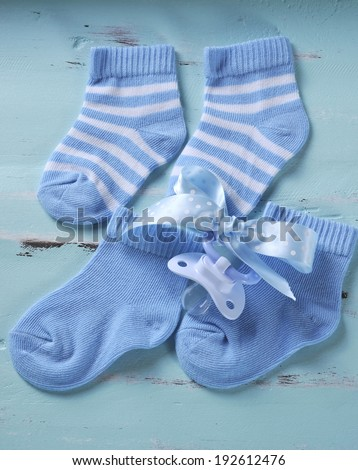 Baby boy nursery blue and white socks and dummy pacifier, on aqua vintage shabby chic background for baby shower or newborn girl greeting card.