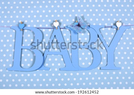 Baby boy nursery blue BABY letters bunting hanging from pegs on a line against a blue polka dot background for baby shower or newborn greeting card. - stock photo