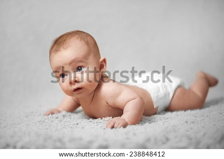 Baby Boy on his stomach learning to lift head - stock photo