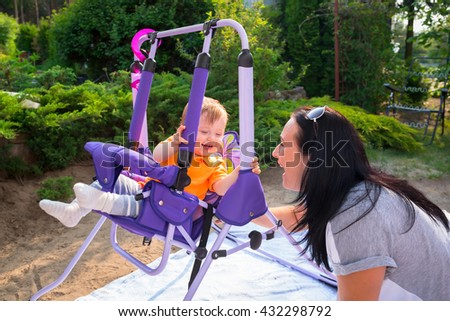 Baby boy on the garden swing with his mother - stock photo