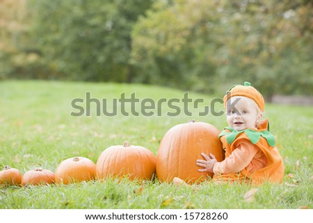 Baby boy outdoors in pumpkin costume with real pumpkins - stock photo