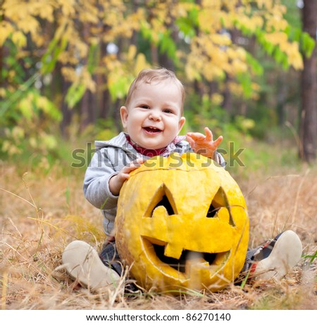 Baby boy outdoors with real pumpkin carved Jack O Lantern - stock photo