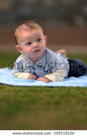 Baby Boy Outside on Blanket. Baby boy laying on a blanket outside while looking down and to the side. Shallow DOF. - stock photo