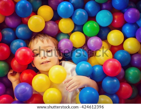 Baby boy playing in pool with colorful balls - stock photo