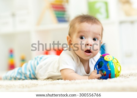 baby boy playing on a carpet at home - stock photo
