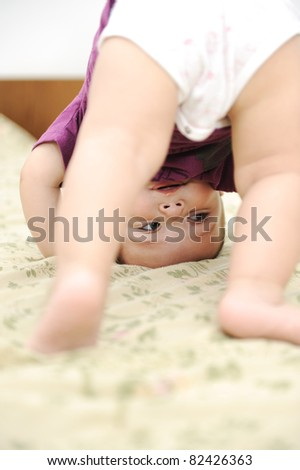 Baby boy playing upside down in bedroom - stock photo