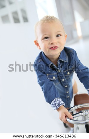Baby boy playing with a riding car toy - stock photo
