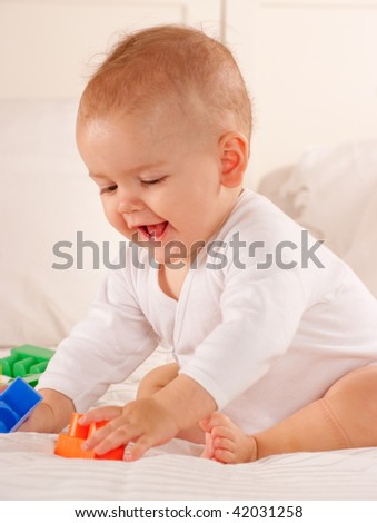 Baby boy playing with bright toy bricks on a bed - stock photo
