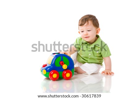Baby boy playing with colorful car toy isolated on white