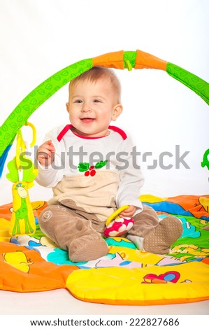 Baby boy playing with colorful toys - stock photo