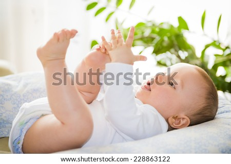 Baby boy playing with his legs - stock photo