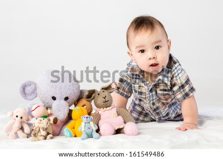 Baby boy playing with knitted toys in studio