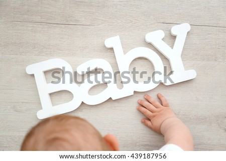 Baby boy playing with letters of the word baby on the floor