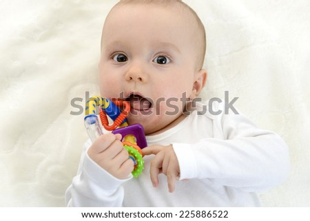 Baby boy playing with teether, toy.