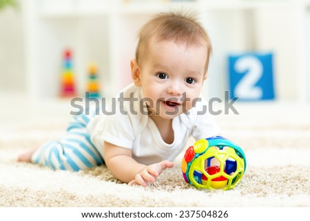 baby boy playing with toys indoors at home - stock photo