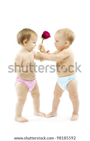 Baby boy present rose flower to a baby girl. Children wear colorful diapers: pink and blue - stock photo