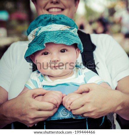 Baby boy riding in infant carrier by mother outdoors at crowded park in vintage filtered image - stock photo