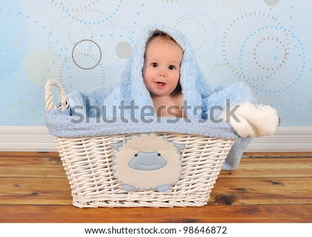 baby boy sitting in basket with blanket on head - stock photo
