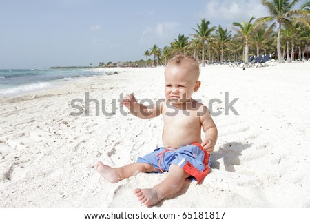 Baby boy sitting on beach, playing in sand