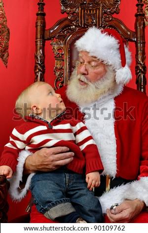 Baby boy sitting on Santa's lap at Christmas time. - stock photo
