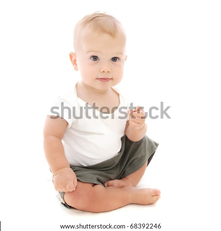 Baby boy sitting on the floor, calm and relaxed - stock photo