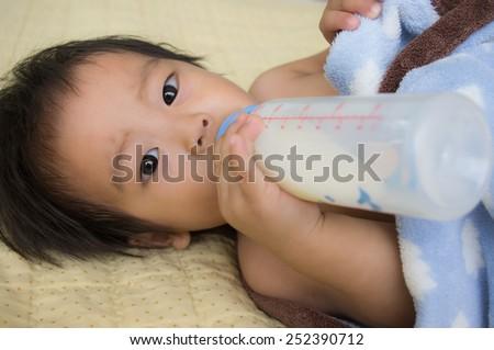 baby boy sleep drinking milk from bottle,Slight frown - stock photo