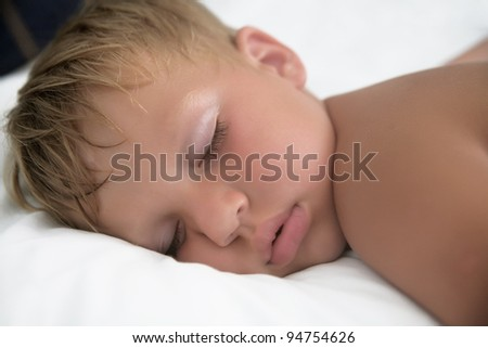 Baby boy sleeping in bed