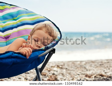 baby boy sleeping on sea beach - stock photo