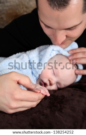 Baby boy sleeping while his father holds his hand