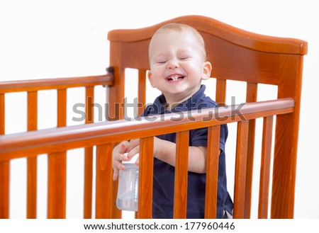 Baby boy standing and laughing in crib - stock photo