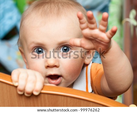 Baby boy standing in cot (crib) and lasts a hand - stock photo