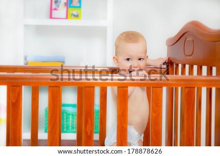 Baby boy standing in crib - stock photo