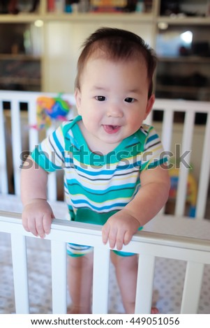 Baby boy stands in his crib. - stock photo