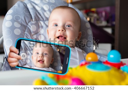 Baby boy taking selfie with a cell phone camera - stock photo