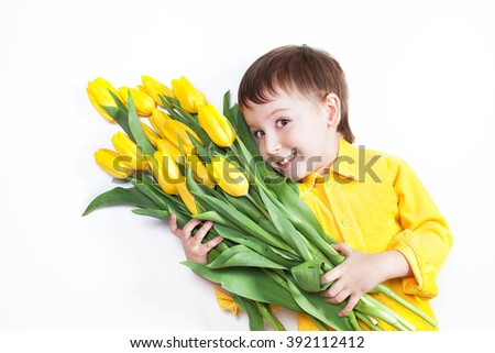 baby boy three years in a yellow shirt lies on a white background in the hands holding a large amount of yellow tulips smiling and want to congratulate my mother. - stock photo